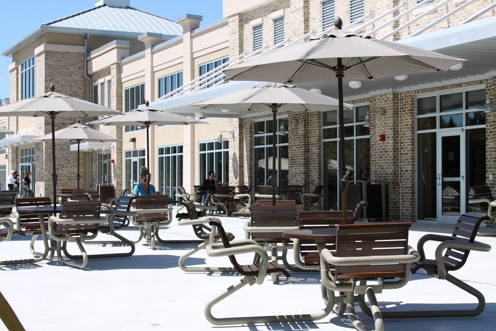 Outdoor eating area with commercial tables and umbrellas