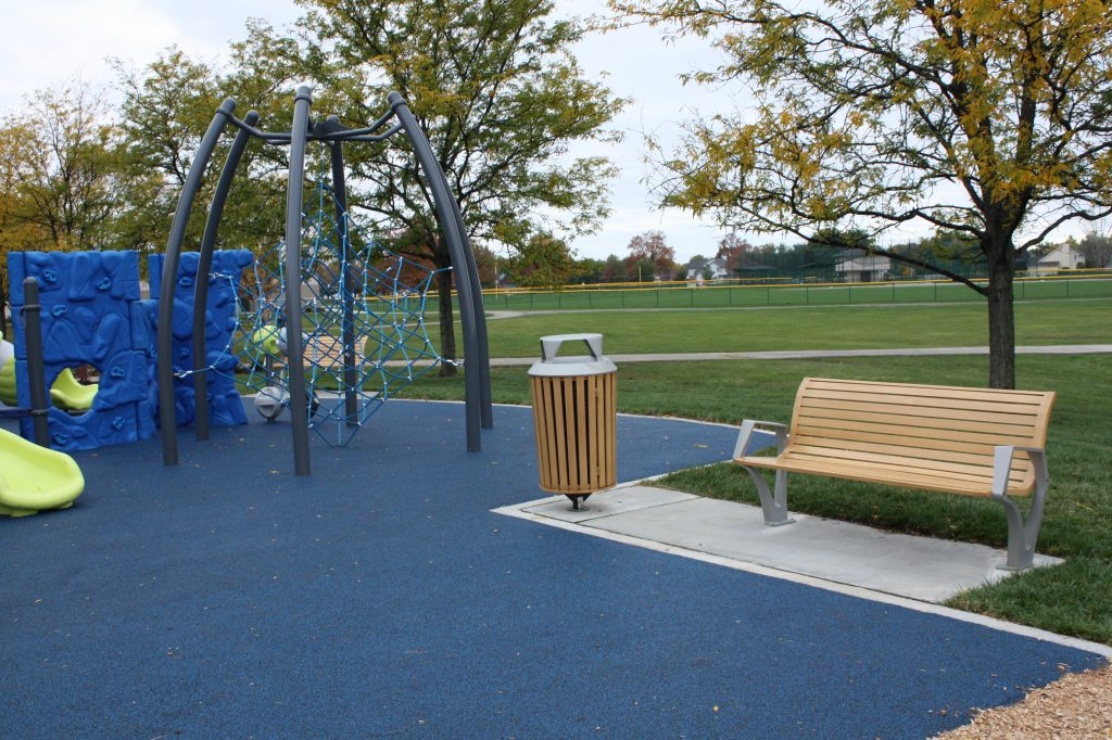 Commercial bench and trash receptacle at park playground